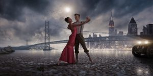 A cross processed image of a vintage retro styled romantic hetrosexual couple dancing in bare feet on a beach a low tide. The dancers are lit by the headlights on a vintage car and are dancing on a deserted beach close to a suspension bridge and city skyscrapers in the background.